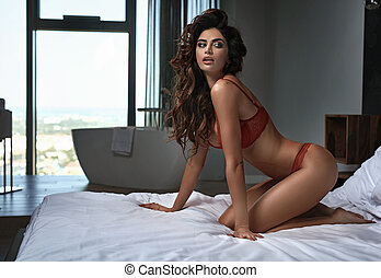 Sexy brunette young woman wearing red lingerie
