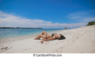 Sexy brunnete in black bikini lying on the beach in summer day and relaxing under the sun. Fit young girl enjoying her tropical vacation passing her time in a lazy way on the ocean coast of Indonesia.