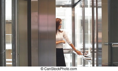 Sexy business lady in glasses uses the Elevator in the office building.