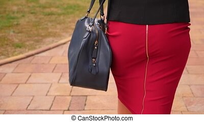 sexy business woman in a red skirt is walking down the...