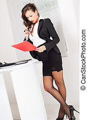 Sexy business woman standing in the office and reading ...