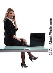 Sexy businesswoman sitting on a desk