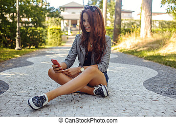 Sexy casual female sitting on the road.