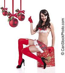 sexy christmas girl sitting on a huge gift box