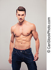Sexy confident man posing over gray background and looking...