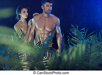 Sexy couple among the tropical plants