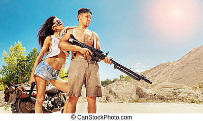 Sexy couple of bikers with guns on the desert background.