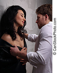 Sexy couple portrait. Man in white shirt with strength hugging his sensual beautiful girlfriend. Closeup