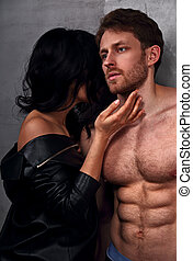 Sexy couple portrait. Man with nude torso touching his sensual beautiful girlfriend neck with much emotion.