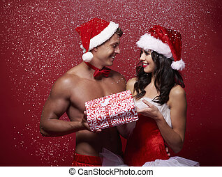 Sexy couple sharing a Christmas present