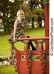 cute woman sitting on handrail at pagoda