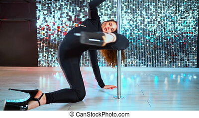 Sexy dancer in black moving in high heels shoes with pylone...