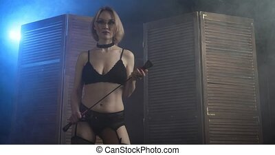 Sexy blond dominant woman in glasses with a whip appears from the wooden folding panel.