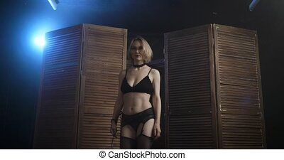 Sexy dominant woman with a whip appears from the wooden...