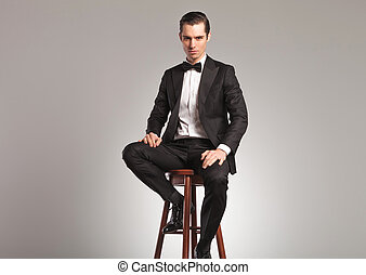 man in tuxedo and bowtie sitting on a stool