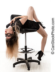 Sexy elegant womanin a little black dress is posing while sitting on a high chair and spreading her legs. girl on a white background