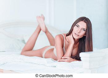 sexy, encantador, niña joven, en, lenceria, mentira en cama