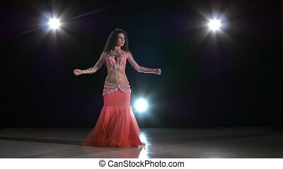 Sexy exotic belly dancer young attractive woman dancing, on black, back light, slow motion