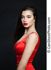 Sexy fashion model brunette with long hair and red lips makeup. Perfect woman on black background