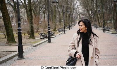 Sexy fashionable woman walking in the autumn park.