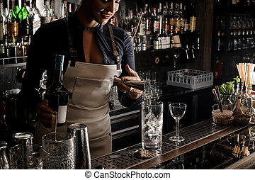 Sexy female barman pouring gin into a cocktail glass - Sexy...