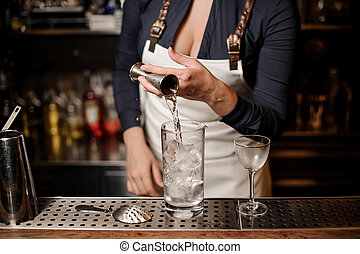 Sexy female barman pouring vodka into a cocktail glass with...