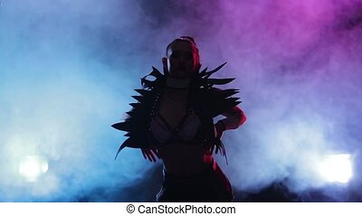 Sexy female disco dancer posing in leather erotic costumes, smoky