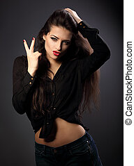 Sexy female model showing rock gesture the two fingers in black shirt and blue short on grey dark grey background
