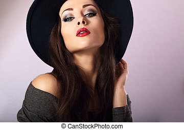 Sexy female model with bright makeup and red lipstick in black hat posing. Closeup fashion portrait