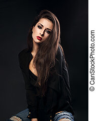 Sexy female model with long brown hair posing in black shirt and ripped jeans on dark background with red lipstick