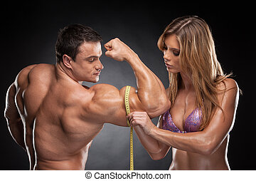 Sexy fit blond woman measure hand male muscular. Standing...