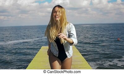 sexy funny girl with long hair running at the camera on the sea background