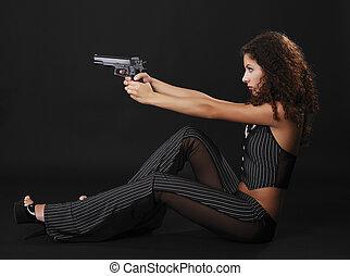 Sexy gangster shooting a handgun.