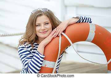Sexy girl against wooden wall in the form of sailors with a lifeline and a cap. Shooting in the studio on a white background.