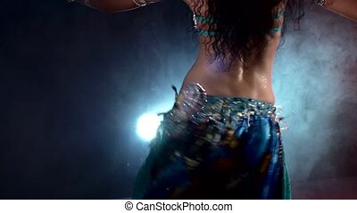 Sexy girl belly dancer arabian in exotic dress dancing, on smoke, back light