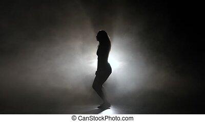 Sexy girl dancing in a smoky studio twerk dance. Silhouette