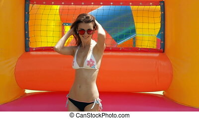 sexy girl in a bathing suit and glasses dancing near inflatable rides