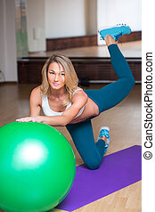 sexy girl in a gym doing yoga on the ball