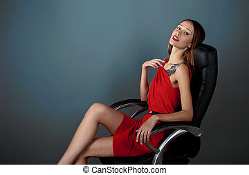 sexy girl in a red dress sitting in leather chair