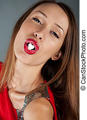 sexy girl in a red dress with sugar in a heart-shaped lips in