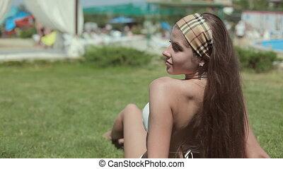 Sexy girl in a white bikini lying on the grass