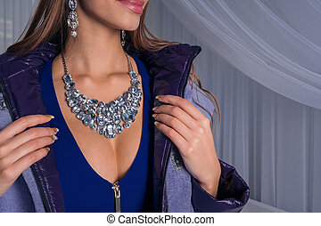 Sexy girl in an expensive fur coat in jewelry with diamonds