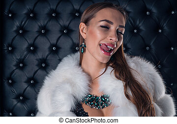 Sexy girl in an expensive fur coat with beautiful earrings and a necklace of precious stones