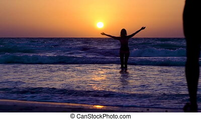 Sexy girl in bikini with boyfriend is having fun, enjoying in ocean. Woman with husband is whirling in the sea. Guy with long hair runs to girlfriend at sunset, carrying girl in water. Happy couple