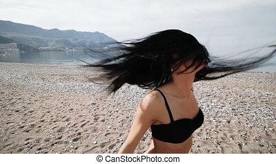 Sexy girl in black bikini swimsuit with a beautiful sports figure dances on the seashore