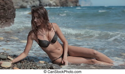 Sexy girl in black bikini with rhinestones having fun lying on the shore of the beach in the waves