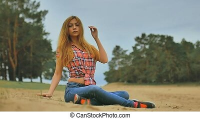 sexy girl in jeans and shirt sitting on the sand in the forest outdoors slow motion