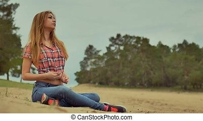 sexy girl in jeans and shirt sitting on sand in forest outdoors slow motion