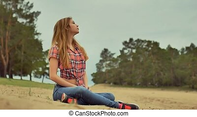 sexy girl in jeans and shirt sitting on sand in the forest outdoors slow motion