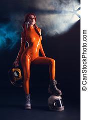 Sexy girl in orange latex catsuit with helmet, sci-fi theme
